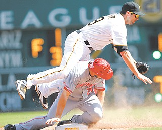 Pittsburgh Pirates second baseman Neil Walker falls over Cincinnati Reds' Chris Heisey as he throws to first to complete the double play on a ground ball by Todd Frazier in the eighth inning of a game Sunday in Pittsburgh.
