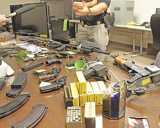Lt. Gerard Slattery, commander of the Youngstown police vice squad, displays an arsenal of firearms, magazines and ammunition, together with drugs and $2,000 in cash, at a Wednesday afternoon news conference. The items were seized in a Tuesday raid on a house at 931 McHenry St. on the city's East Side.
