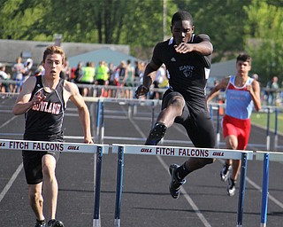 Valantino Sewell of Youngstown East jumps over the final hurdle to take first place in the mens 300 meter hurdle while being followed closely by Andrew Hamilton of Howland during Fridays Division one district championship track meet at Austintown Fitch High School.  Dustin Livesay  |  The Vindicator