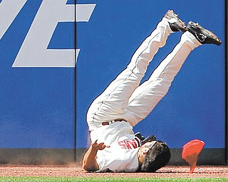 Cleveland Indians left fielder Johnny Damon flips upside down after slamming into the outfield wall on an RBI-double by the Miami Marlins' Logan Morrison in the eighth inning of Sunday's interleague baseball game in Cleveland. The Indians fell 5-3.