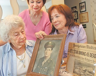 Rosemary McIntire, left, recalls memories of her first husband, Maurice Hamilton, who was killed in a plane bombing. Two of her daughters, Roseann Cencia, center, and Teresa Kondis, right, discuss their father and how their lives changed after his death. Hamilton and 44 others were killed May 22, 1962, when a bomb placed in the plane's bathroom brought the aircraft down over the Iowa/Missouri line.