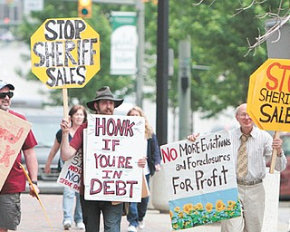 Sean O'Toole, left, Joshua Kessner and Jim Villani protest the Mahoning County sheriff 's sale of homes that were to be auctioned off Tuesday. O'Toole and Kessner are members of Occupy Youngstown. The Occupy group says land banks should be used to hold and transfer property.