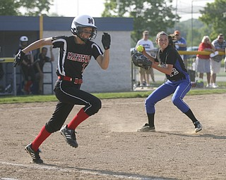JESSICA M. KANALAS  | THE VINDICATOR..Jackson Milton's #12 Paije Kiraly grounds a bunt in the top of the fifth inning as Mathews #7 Maddie Williams heads for first base during the Division 3 Regional Semifinal game at Kent State University.