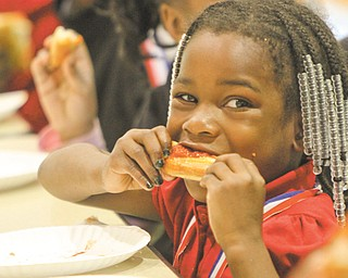 Cyra Cross, a member of the Principal's Club, digs into a slice of pizza at the party.