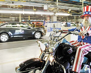 """Gary """"Bones"""" Mowen of Niles wears an Uncle Sam costume as he rides his Harley-Davidson motorcycle through the General Motors Lordstown plant as part of a fundraising ride Thursday."""