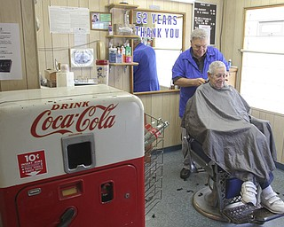 William D Lewis The Vindicator    Long time Youngstown barber Cosmo Pecchia gives a trim to Tom Shimet of Girard. Pecchia opened the shopin 1962 in the house on Oak St where he grew up. The Coke machine still has cokes for a dime.
