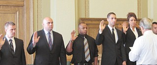 Youngstown's nine newest police officers — Michael Sobnovsky, Phillip Skowron, Martin Stachowicz, Ryan Curry, Mohammed Awad, Jessica Shields, Robert Gentile, Seann Carfolo and Christopher Staley — are sworn in by Mayor Charles Sammarone on Tuesday.