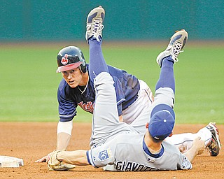 Kansas City Royals second baseman Johnny Giavotella is upended after forcing out the Cleveland Indians' Luke Carlin then throwing to first to complete a double play during the fourth inning of Tuesday's baseball game in Cleveland. The Royals downed the Indians, 8-2.