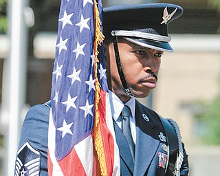 Mark White of the 910th Air Reserve Station Honor Guard carries the U.S. flag before the Reading of the Names ceremony at Youngstown State University on Wednesday.