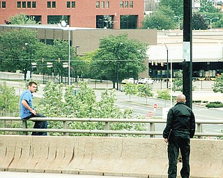 John Sylvester Jr. sits on the Market Street bridge Sunday as a police official talks with him. Sylvester was wanted for a stabbing incident in Boardman earlier in the day and fled to the bridge, where for four hours he kept police at bay with threats to jump before finally surrendering.