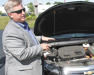 The Vindicator Randy Summer Director Global Hybrid Electric Vehicle Business and Technology demonstration Thursday in Champion looks under the hood of a Chevy Volt during Green Enegy event in Champion.