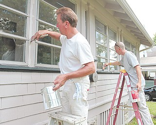 Mike Daugherty, left, and Ernie Avery of Avery Painting, spruce up a home in the city's 7th Ward under Paint Youngstown, a city program that pays for minor repairs to homes that are facing code violations.