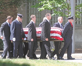 Pallbearers carry the coffin of Warren firefighter Marc Titus into the W.D. Packard Music Hall in Warren. Bugler Garey Watson, top, played taps during the funeral Thursday. Titus, 46, of Cortland, died a week ago in a motorcycle crash on state Route 11 near the King-Graves Road overpass.