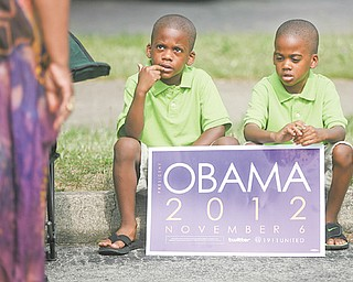 Twin brothers Brycen and Brayden Mahone, 5, of Youngstown hold their re-election sign at the rally for President Barack Obama and voter-registration drive at the former Mr. Paul's Bakery at Glenwood and Parkview avenues in Youngstown. The event, sponsored by 1911 United, which consists of current and former members of Kappa Alpha Psi and Omega Psi Phi fraternities, took place Sunday afternoon. Below, Jermal Giles, 22, a member of 1911 United and Omega Psi Phi, performs for the crowd.
