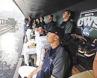 Kent State players wait in the dugout as heavy rain drenches the field before their College World Series