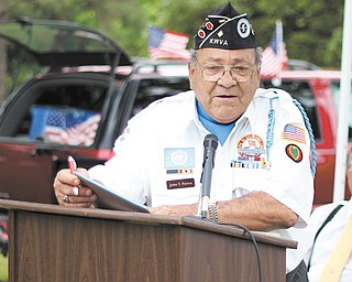 Commander John Pariza of the Korean War Veterans Association of Mahoning Valley Chapter 137 makes opening remarks at Veterans Park at Wickliffe Circle in Austintown on Sunday during the Korean War Veterans' Laying of the Roses ceremony.