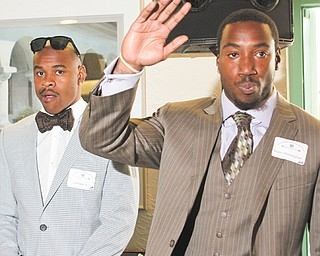 Warren Harding High graduate Mario Manninghan, right, waves, while former Ohio State receiver Ted Ginn Jr., left, looks on during a DeBartolo Foundation dinner Monday at Leo's in Howland.