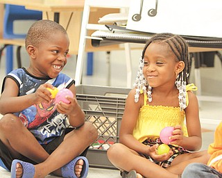 Jeremiah Payne, left, and Aniya Pilson, both 5, share a few laughs playing with stress balls at a Success By Six event at Williamson Elementary School in Youngstown. The youngsters learned Wednesday what is necessary to become good students and citizens.