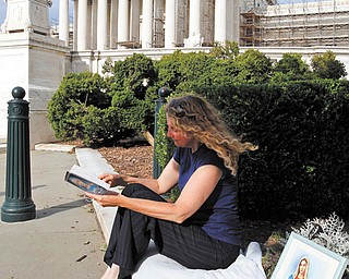 Carol Anderson of Williamsburg, Va., reads as she is the first person in line to attend today's reading of the decision at the U.S. Supreme Court on the constitutionality of the Affordable Care Act. She started the line Wednesday afternoon.