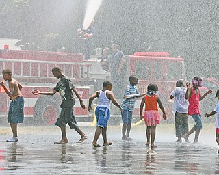 """Children from the Plaza View Apartments community cool off in water shot from the hose of Engine 12 of the Youngstown Fire Department. The firefighters came out to teach the kids not to be afraid of the firetrucks they see on a daily basis. City Youth director Andrea Mahone runs summer activities for the children in the apartment complex, which is the only public housing in the city without a youth center. Mahone said the program, called """"Increase the Peace,"""" was implemented into the community to """"make them respect and love the city of Youngstown."""""""