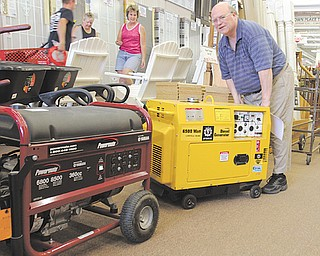 Bill Clark, manager of Bernard-Daniels Lumber and Hardware in Canfield wheels a diesel generator from the business, while a gas-powered generator sits on the floor. The company had put its generators on eBay Sunday night and sold several to people affected by the outages in central Ohio.