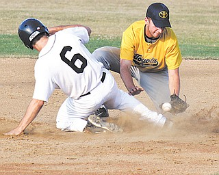 The Astro Falcons' Jake Froats scrambles safely back to second as Toyota of Warren's Tony Mehle bobbles the ball during a pick-off attempt during Monday's Class B baseball playoff game at Cene Park in Struthers. Astro defeated Toyota, 2-0, to advance to the championship today against Creekside Fitness.