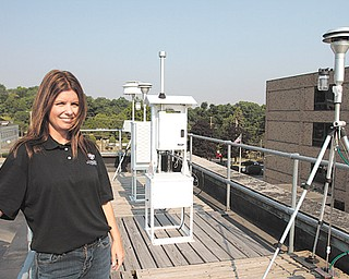 Administrator Tara Cioffi of the Mahoning-Trumbull Air Pollution Control Agency checks the air-quality monitoring equipment on the roof of the building next to Oakhill Renaissance Place at 345 Oak Hill Ave. in Youngstown.
