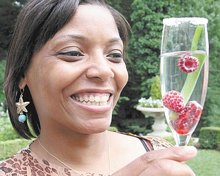 """Kena Perkins, Springfield Grille's service manager, holds a drink made with locally grown raspberries. She is involved with the menu that will be offered at the Friends of the Fellows Riverside Gardens' """"Sugar Beets Meet City Streets"""" Garden Party set for July 27. Photo by WILLIAM D. LEWIS 
