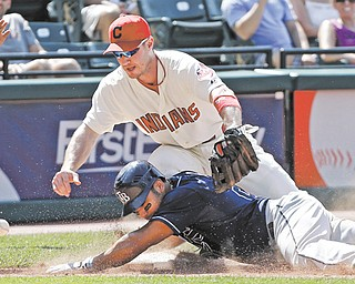 Tampa Bay Rays' Carlos Pena, bottom, slides into third with an RBI triple as the throw eludes Cleveland Indians third baseman Jack Hannahan in the ninth inning of a baseball game Sunday in Cleveland. The Rays scored three runs in the inning off Indians closer Chris Perez to win 7-6.