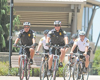 Officers, from left, Sgt. Dennis Godoy and Chief John Beshara of the Youngstown State University Police; second row, from left, Alki Santamas and Dave Moss, both of the Mahoning County Sheriff 's office; and back row, Christian Hunter of Mill Creek MetroParks Police; unveiled YSU Police's bike patrol unit Monday.