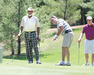 Former Steelers defensive end LC Greenwood, left, watches as Eric Folsom putts on No. 10 at Monday's Circle of Friends Celebrity Golf Classic at the Lake Club in Poland. At right, Rob Folsom looks on.