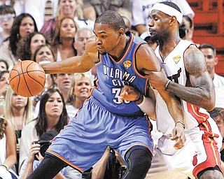 Oklahoma City Thunder forward Kevin Durant, left, works the ball against Miami Heat forward LeBron James during the first half of Game 5 of the NBA finals in Miami. Durant and James will team up for the USA in this summer's Olympics.