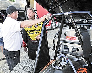 NASCAR driver Dave Blaney talks to a member of his race team after a hot laps race Tuesday night at the Sharon Speedway.