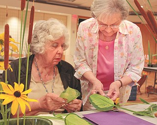 Shirley Winkler of Saxonburg, Pa., right, assists Pearl Marlos of Campbell as she creates a floral arrangement in the style of Ichiyo, one of numerous schools of Ikebana. Winkler has been teaching Japanese flower arranging for more than 30 years. Photo by: Robert K. Yosay | The Vindicator