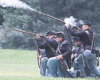 A group of Union soldiers fires muskets loaded with blanks during a battle scene during the Civil War re-enactment in Argus Park in Canfield. Re-enactors from both the Union and Confederate sides of the war took up camp in the park Friday through Sunday.