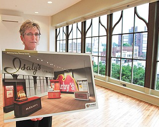 Cheryl Lewis, the Mahoning Valley Historical Society's campaign director, shows plans for the third floor of the Tyler Mahoning Valley History Center. The floor will feature portable hands-on exhibits from some of the city's iconic businesses, including Isaly's, McKelvey's and Arby's.