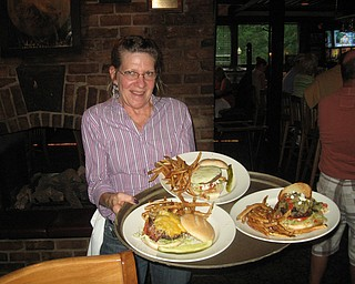 Barby Ferraro serves up some tasty Iron Bridge Inn burgers. Clockwise from left are The Western Burger, The Pittsburger and the Big Greek Burger.