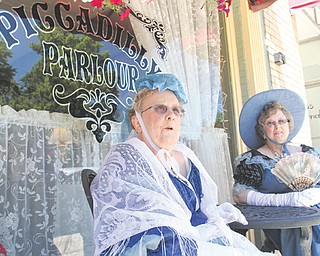 Sisters Barbara Urich, left, and Eleanor Urich sit outside Piccadilly Parlour in Canfield on Wednesday afternoon. Wish of a Lifetime, an organization that grants wishes for senior citizens, helped Barbara Urich fulfill her dream to wear a Victorian-era gown during lunch with her family.