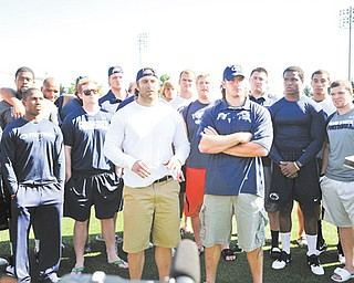 """Members of the Penn State football team flank senior fullback Michael Zordich, left foreground, and senior linebacker Michael Mauti, right foreground, as the pair made a statement of support for their team on Wednesday in State College, Pa. More than 30 players came together as Zordich, a Cardinal Mooney graduate, and Mauti announced to the world: """"We're going to see this thing through,"""" then they all walked off the field together and back into the building."""