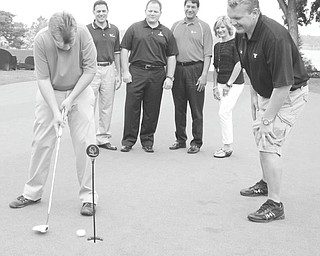 Chris Marchionda, 21, a graduate of the Rich Center For Autism, putts as YSU football coach Eric Wolford offers advice. In rear from left are Chris Colella of First National Bank, Rick Cook of Simon Roofing, Pete Asimakopoulos of First National Bank and Jackie Marchionda, mother of Chris. The Rich Center's annual fundraiser, PAR Golf Outing, is scheduled for Aug. 27. Photo by WILLIAM D LEWIS | THE VINDICATOR