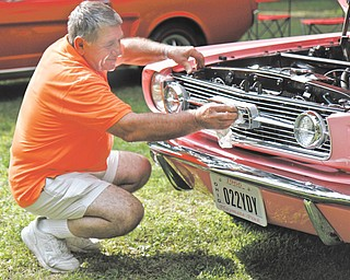 Sam Martuccio shines his daughter's car at the Thunder in the Park car show in Woodland Park in McDonald. He restored the 1966 Mustang for his daughter, Lucua.
