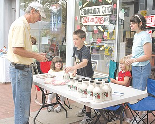 Patrick, 9, Abigail, 7, and Katherine, 3 sell their familie's homemade maple syrup with their mother Mary Wolfgang, of Hanoverton. Their first customer of the day, Lou Markovich of Salem said his favorite local product at the market is the syrup.
