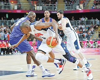 USA's Kevin Durant drives to the basket past France's Ali Traore during the first half of a preliminary men's basketball game at the 2012 Summer Olympics on Sunday in London. The USA won 98-71.