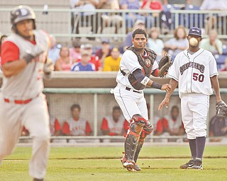 Mahoning Valley Scrappers pitcher Luis Morel watches as catcher Charlie Valerio (16) fi res the ball to fi rst base to get Brooklyn Cyclones base runner Alex Sanchez out during Monday's New York-Penn League game at Eastwood Field, Niles. The Scrappers fell to the Cyclones, 5-1.