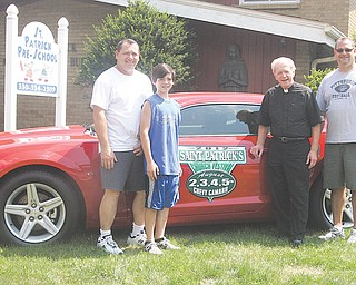 From left, Bill Fisher, St. Patrick's festival chairman, Joey Fisher, the Rev. Tim O'Neill and Matt Fisher show off the new 2012 Chevy Camaro that will be given to a lucky winner Sunday night. St. Patrick's annual festival runs Thursday through Sunday at the church in Hubbard.