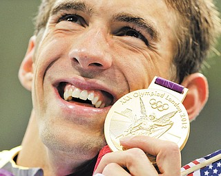 United States' Michael Phelps poses with his gold medal for the men's 4x200-meter freestyle relay swimming final at the Aquatics Centre in the Olympic Park during the 2012 Summer Olympics in London on Tuesday.