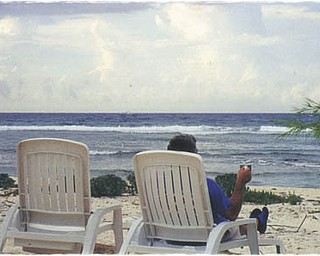"""John Ploskodniak sent in this photo of his brother taken at Little Cayman Islands. John said his brother wanted a picture of two chairs by the ocean with the caption, """"There is always a chair waiting for you."""""""
