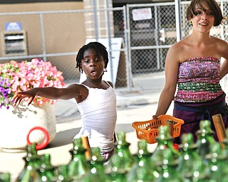 Anjela Taylor, 7, plays a ring toss game while Rebecca Mounts gives her careful instructions on the best way to win a prize.