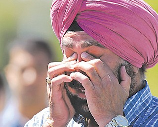A man reacts outside the Sikh Temple of Wisconsin to a shooting there that killed at least six.