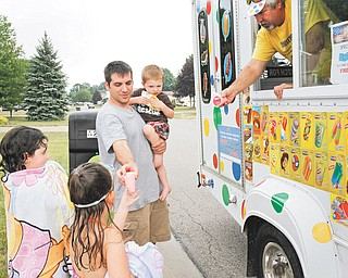 James Naughton, 2, Abbigail Yavorski, 7, and Lilly Naughton, 6, receive their treats from ice-cream truck vendor Joe Harrison after a swim in their pool.